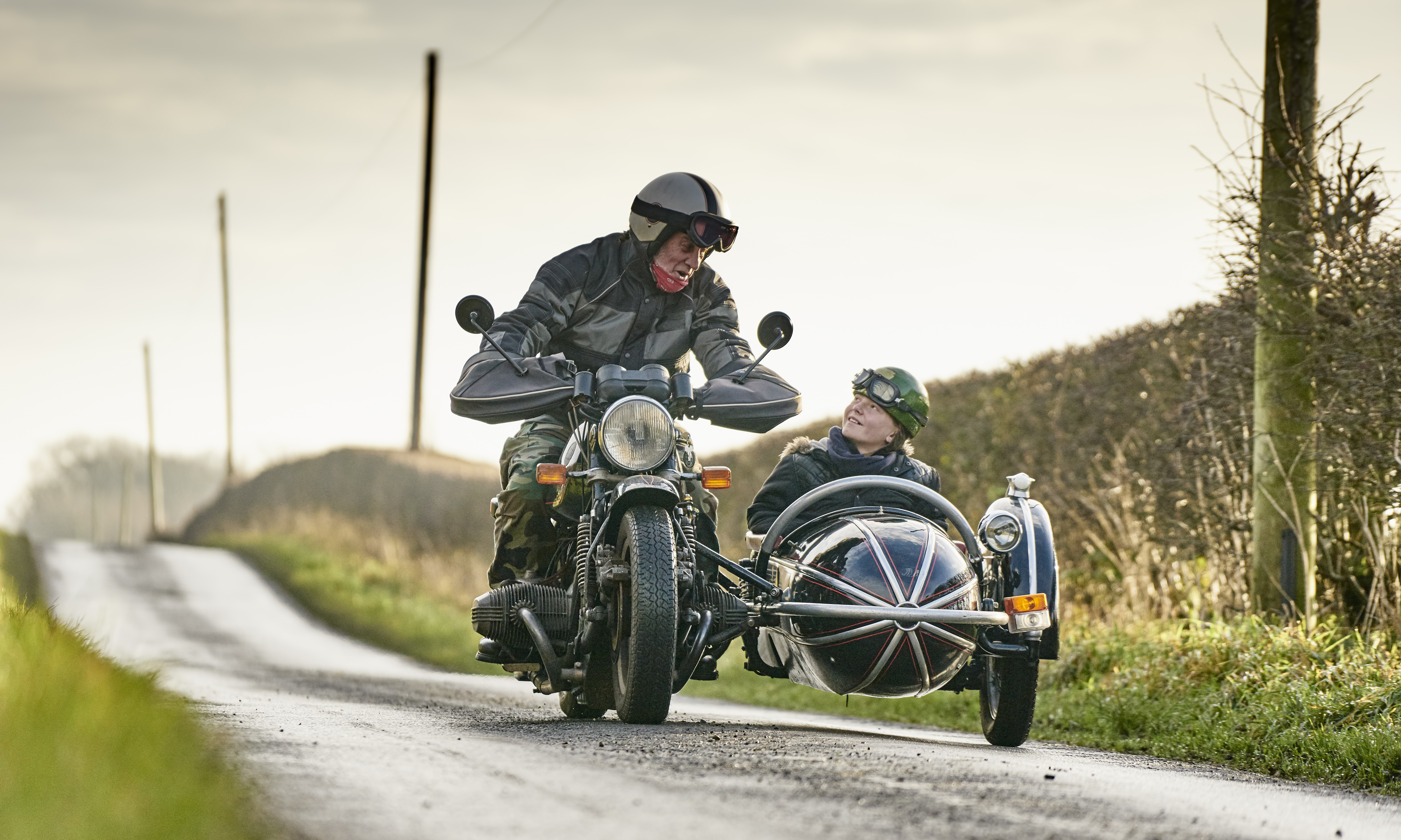 Senior man and grandson riding motorcycle and sidecar along rural road